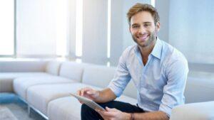 Mann sitzt mit iPad auf Couch und lächelt