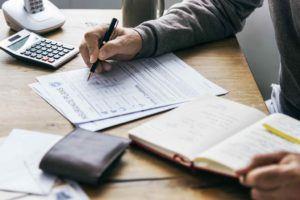 Mann schreibt Kündigung für die Lebensversicherung auf Papier