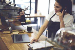 Frau telefoniert im Cafe mit Anwalt