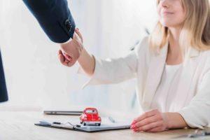 Anwalt gibt Frau die Hand während Unterzeichnung eines Sachdarlehensvertrag