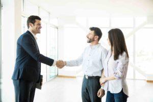 Wohnungseigentümer schüttelt Käufern die Hand