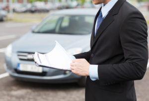 Ein Mann im Anzug hält Vertrag in der Hand. Ein Auto im Hintergrund ist zu sehen.