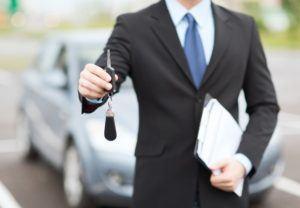Ein Mann im Anzug hält Vertrag und Schlüssel in der Hand