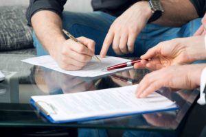 Mann unterschreibt etliche Dokumente