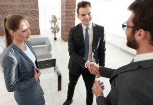 Geschäftsmänner reichen sich die Hand. Frau schaut zu.