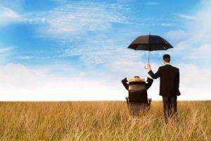 Sitzende Mann wird mit Regenschirm geschützt