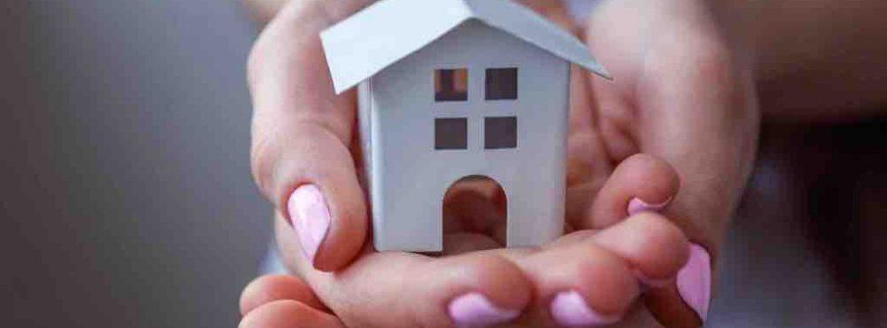 Mensch hält ein Miniaturhaus in Händen