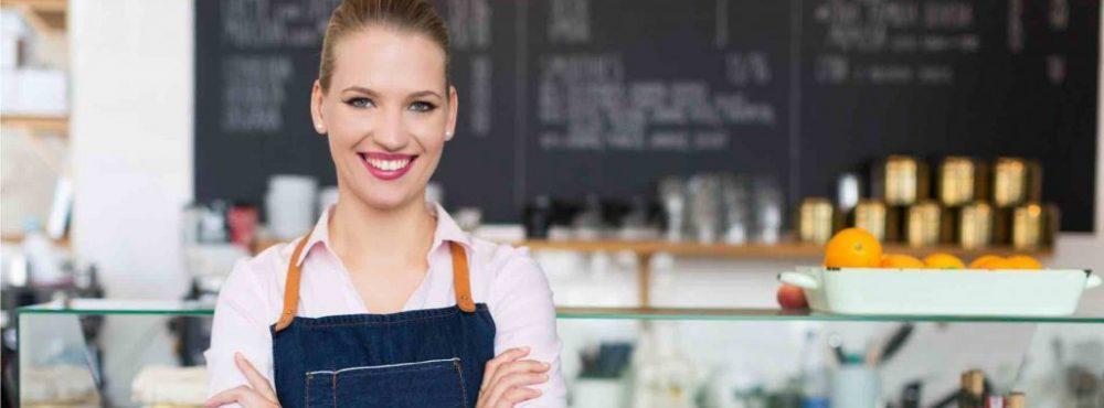 Frau steht in einem Restaurant und verschrenkt die Arme