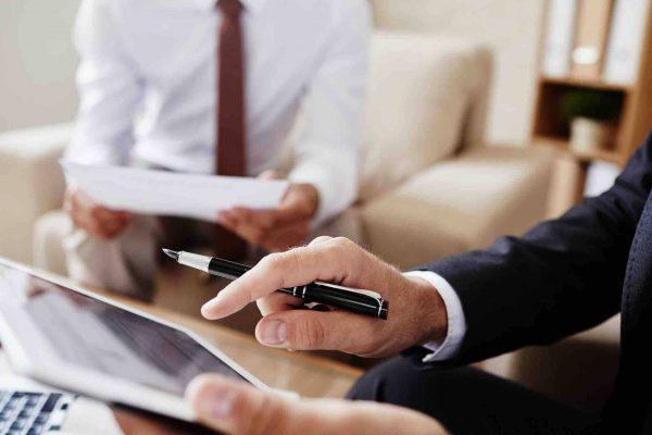Anwalt geht mit Klienten einen Vertrag durch